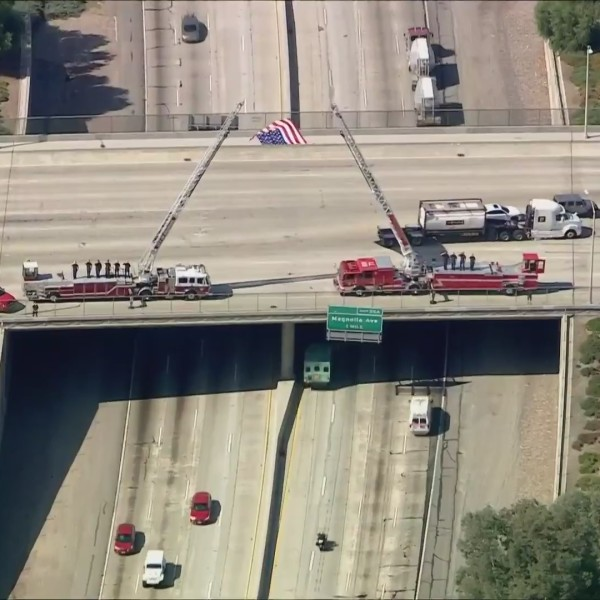 Firefighters salute as a procession for Charles Morton passes on Sept. 22, 2020. (KTLA)