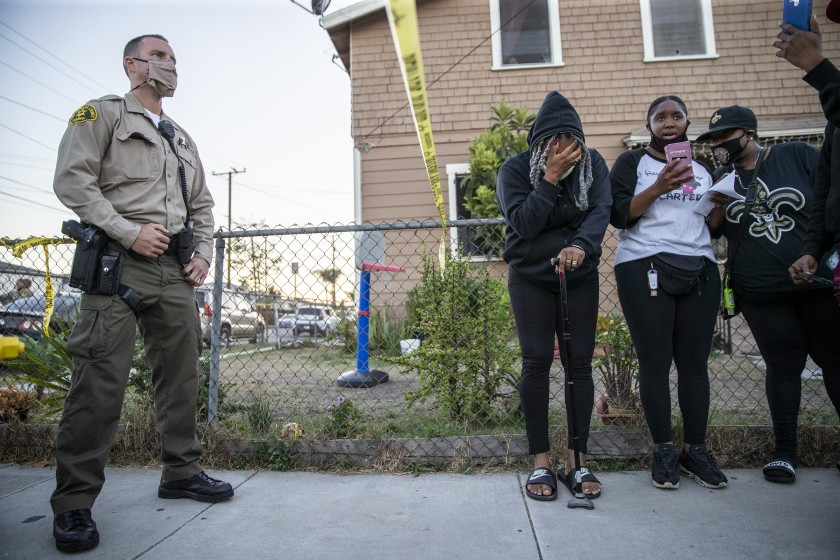 An L.A. County sheriff's deputy stands behind a caution tape as a group of mourners stand on the other side after the deputy killing of Dijon Kizzee in the Westmont neighborhood on Aug. 31, 2020. (Robert Gauthier / Los Angeles Times)