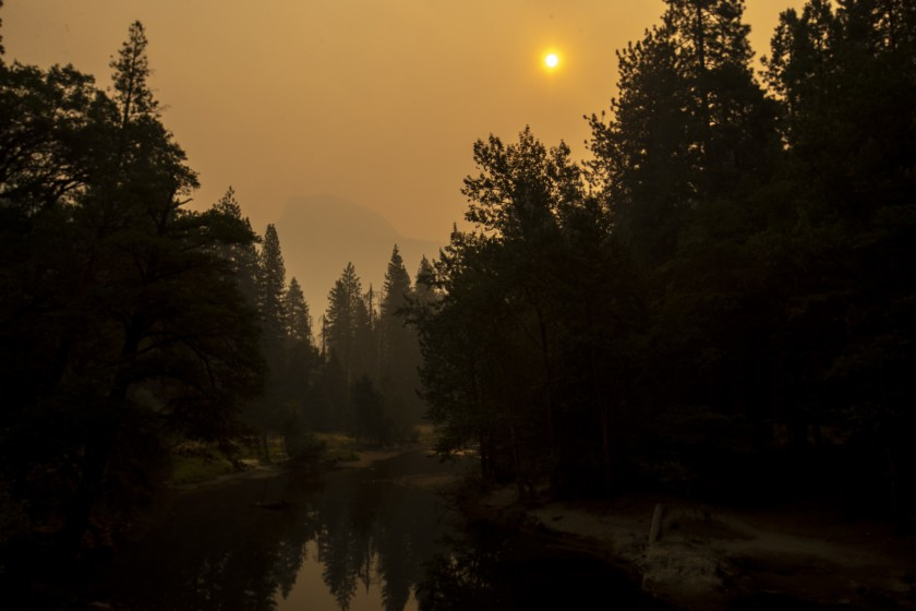 Thick smoke shrouds Half Dome over Yosemite Valley in a view from Sentinel Bridge over the Merced River on Sept. 13, 2020. (Brian van der Brug/Los Angeles Times)