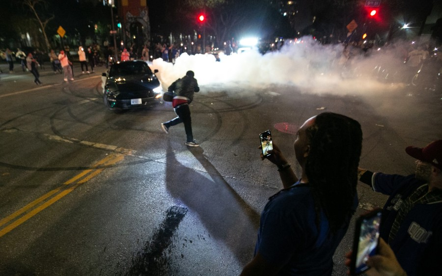 Fans watch a car do burnouts in downtown Los Angeles following the Los Angeles Dodgers World Series win over the Tampa Bay Rays on Oct. 27, 2020. (Jason Armond / Los Angeles Times)