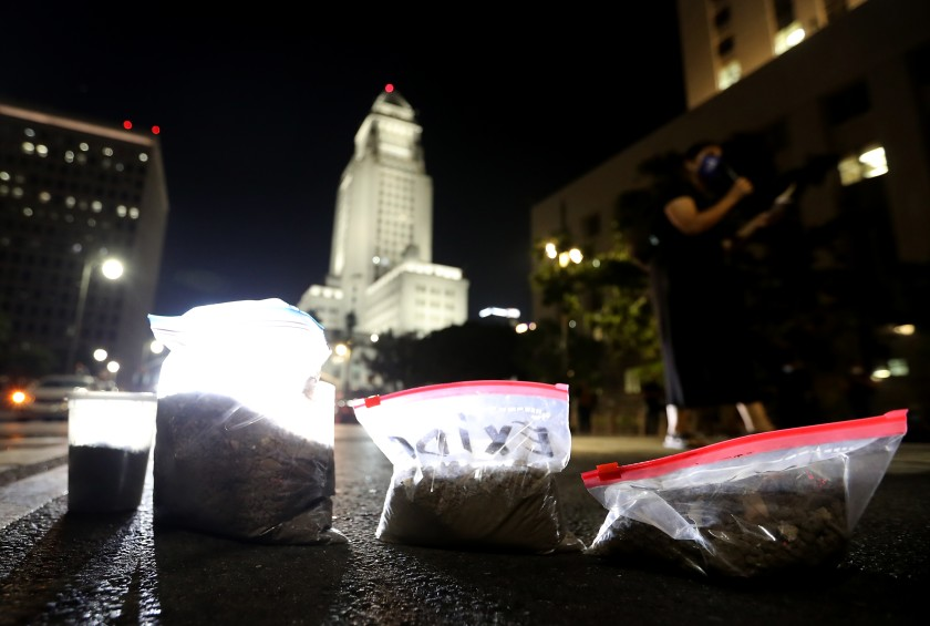 Protesters left bags of lead-contaminated dirt in downtown L.A. on Oct. 19, 2020, during a demonstration against a court ruling allowing owners of the Exide battery recycling plant in Vernon to abandon the facility, leaving the cleanup to California taxpayers. (Luis Sinco / Los Angeles Times)