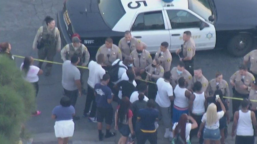 Bystanders and law enforcement exchange words at the scene where deputies shot and killed a man in Willowbrook on Oct. 16, 2020. (KTLA)