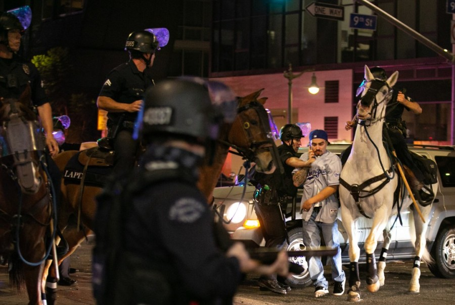 LAPD officers on horseback move in to disperse the crowds in downtown Los Angeles after the Dodgers won the World Series on Oct. 27, 2020. (Jason Armond / Los Angeles Times)