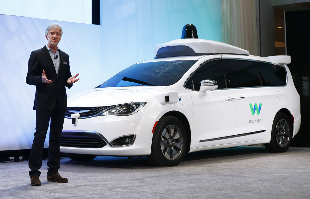 In this Jan. 8, 2017, file photo, John Krafcik, CEO of Waymo, the autonomous vehicle company created by Google's parent company, Alphabet, introduces a Chrysler Pacifica hybrid outfitted with Waymo's own suite of sensors and radar, at the North American International Auto Show in Detroit. (AP Photo/Paul Sancya, File)