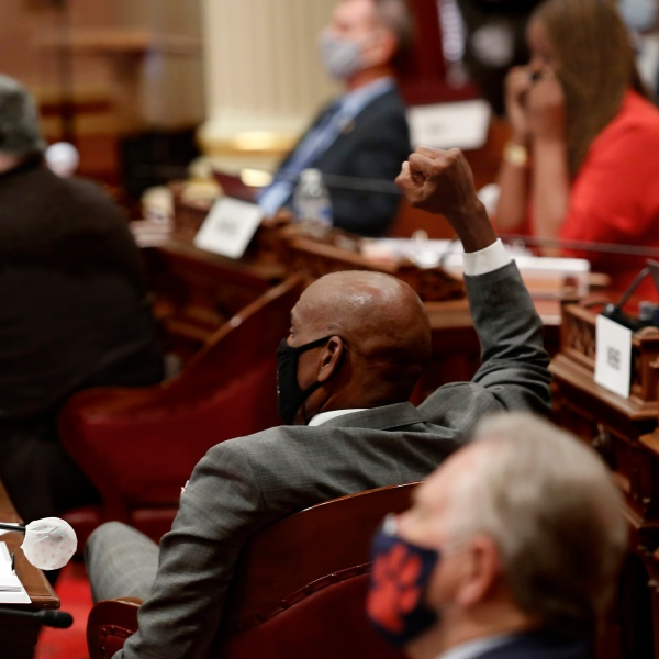 State Sen. Steve Bradford, D-Gardena, center, raises his fist in celebration as the Senate approves a measure to place a proposed Constitutional amendment on the November ballot to overturn its ban on affirmative action programs, at the Capitol, in Sacramento, June 24, 2020. (AP Photo/Rich Pedroncelli)