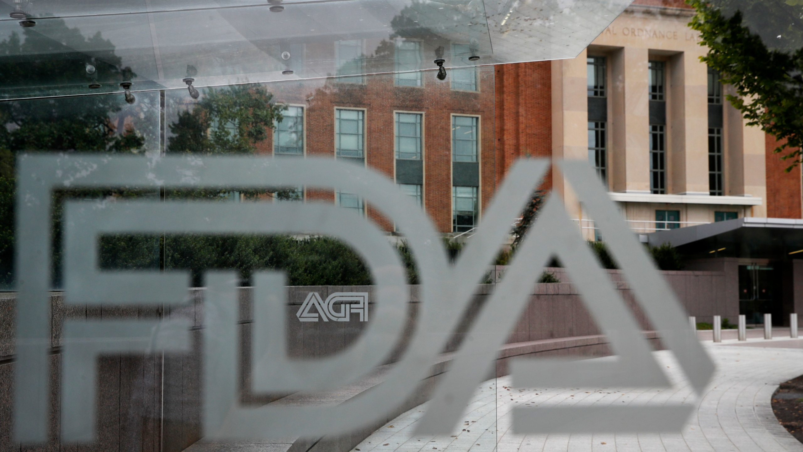 """This Aug. 2, 2018, file photo shows the U.S. Food and Drug Administration building behind FDA logos at a bus stop on the agency's campus in Silver Spring, Md. In a report to Congress and an accompanying """"playbook"""" for states and localities, key federal health agencies and the Defense Department sketched out complex plans for a vaccination campaign to begin gradually early next year or later in 2020, eventually ramping up to reach any American who wants a shot. The Pentagon is involved with the distribution of vaccines, but civilian health workers will be the ones giving shots. (AP Photo/Jacquelyn Martin, File)"""