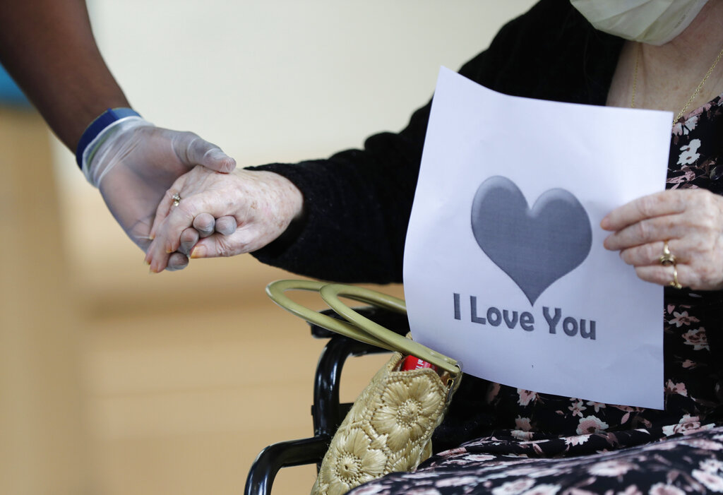 In this July 17, 2020 file photo, a senior citizen holds the hand of a care coordinator at a Health facility in Miami. (AP Photo/Wilfredo Lee)