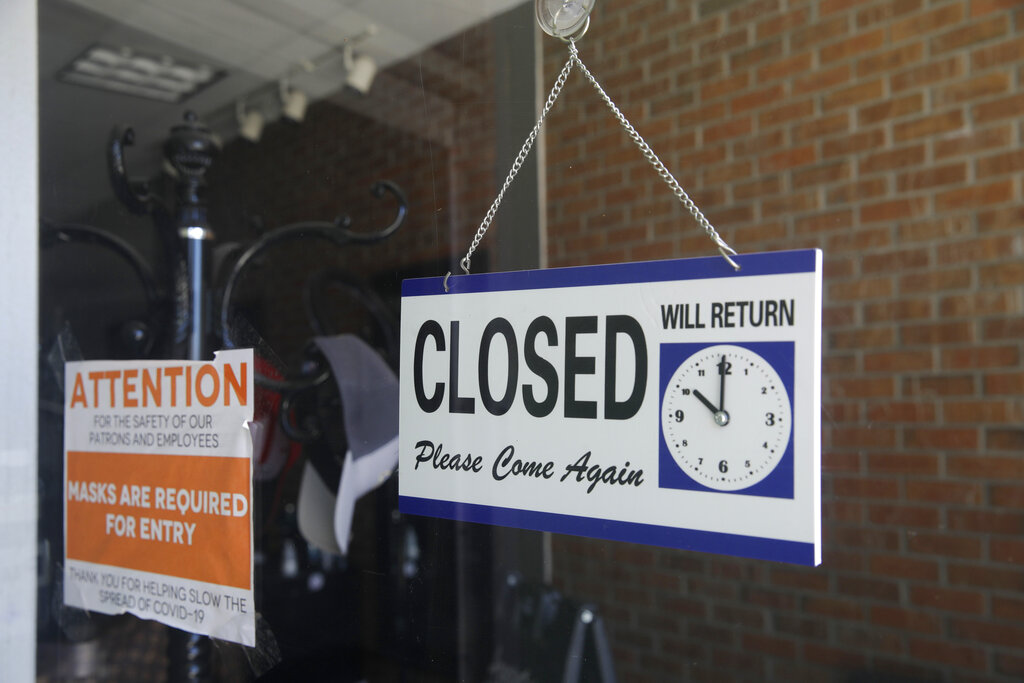 In this July 18, 2020 file photo a closed sign hangs in the window of a barber shop in Burbank, Calif. (AP Photo/Marcio Jose Sanchez, File)