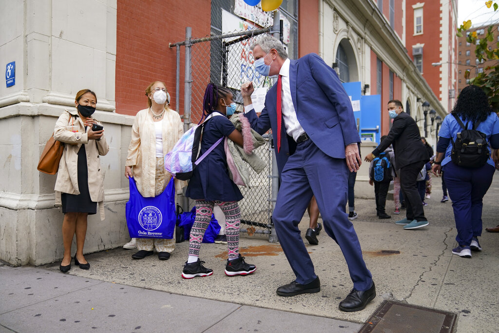 New York Mayor Bill de Blasio, center right, greets students as they arrive for in-person classes outside Public School 188 The Island School on Sept. 29, 2020, in the Manhattan borough of New York. (AP Photo/John Minchillo)