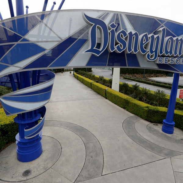 About 10,000 of the 28,000 layoffs in the company's parks division will be hitting the Disneyland Resort parks, hotels and stores in Anaheim, according to company sources. Notifications for those layoffs are expected to reach workers via email by Sunday. This file photo from March 18, 2020 shows one of the normally bustling entrances to the Disneyland Resort. (AP Photo/Chris Carlson, File)