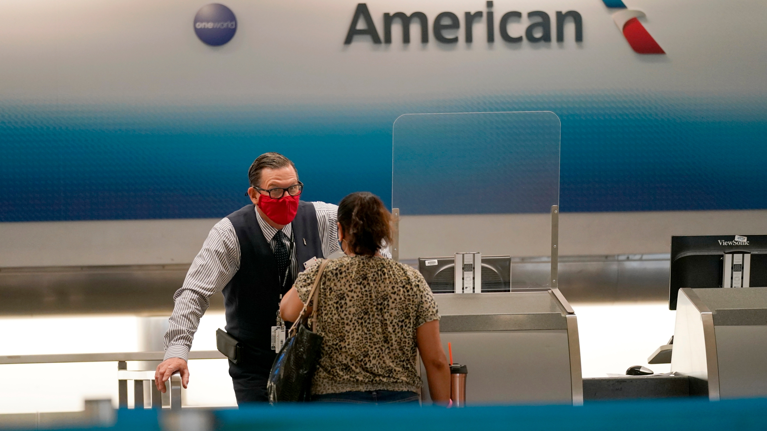 An American Airlines ticket agent works with a customer at Miami International Airport during the coronavirus pandemic on Sept. 30, 2020, in Miami. (AP Photo/Lynne Sladky, File)