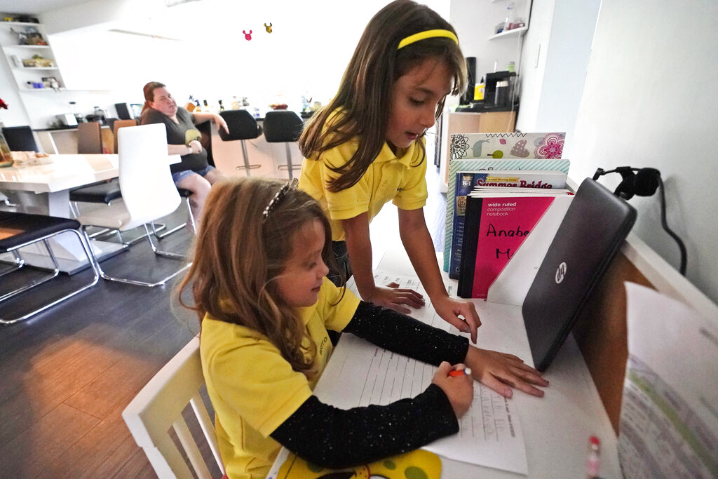 Emily Chao, standing, watches as her sister Anabelle, works on a writing exercise after they finished remote learning for the day on Oct. 1, 2020, at their home in North Miami Beach, Fla. Rather than wait to see how the Miami-Dade school system would handle instruction this fall, Erica Chao enrolled her two daughters in a private school that seemed better positioned to provide remote learning than their public elementary school was when the coronavirus first reached Florida. (AP Photo/Wilfredo Lee)