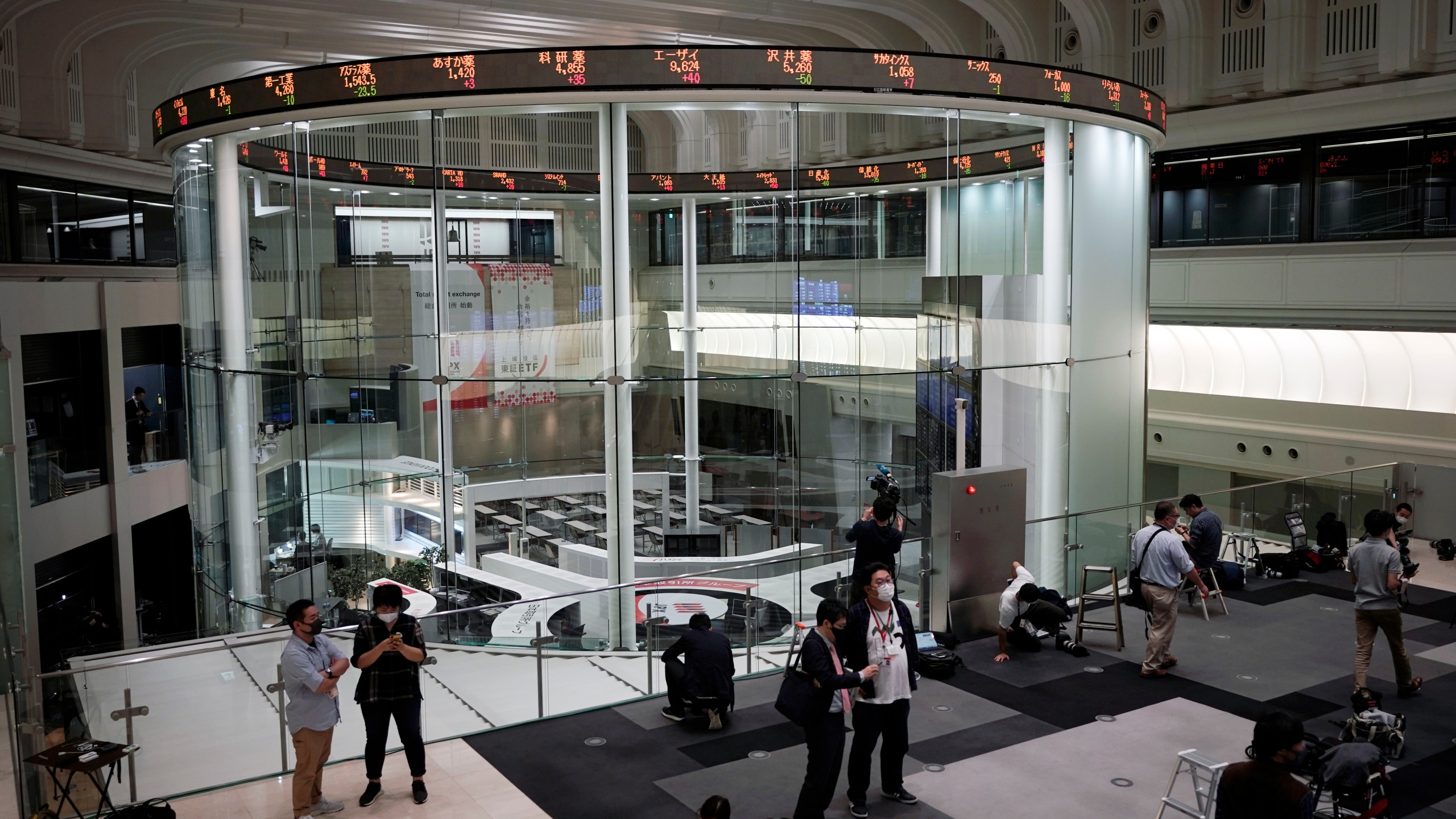 Journalists film an electronic stock board showing reopened Japan's Nikkei 225 index at Tokyo Stock Exchange on Oct. 2, 2020. (AP Photo/Eugene Hoshiko)