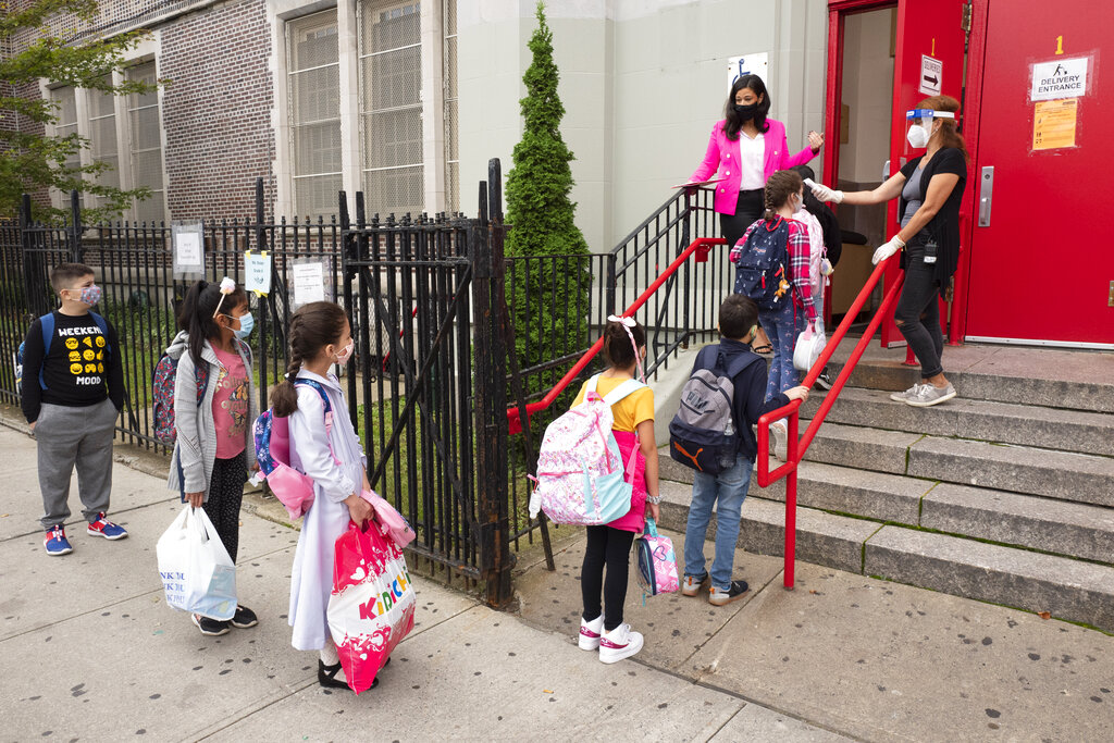 In this Sept. 29, 2020, file photo, students line up to have their temperature checked before entering PS 179 elementary school in the Kensington neighborhood in the Brooklyn borough of New York. (AP Photo/Mark Lennihan, File)