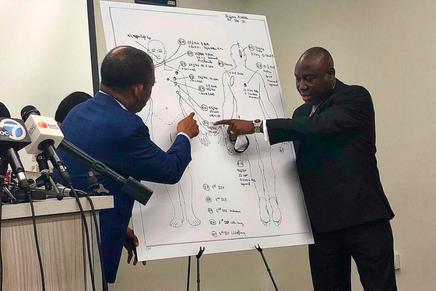 Attorneys Carl Douglas, left, and Benjamin Crump, right, point to bullet wounds on a diagram of Dijon Kizzee's body as part of an independent autopsy during a news conference in Los Angeles on Sept. 22, 2020. (AP Photo/Stefanie Dazio, File)
