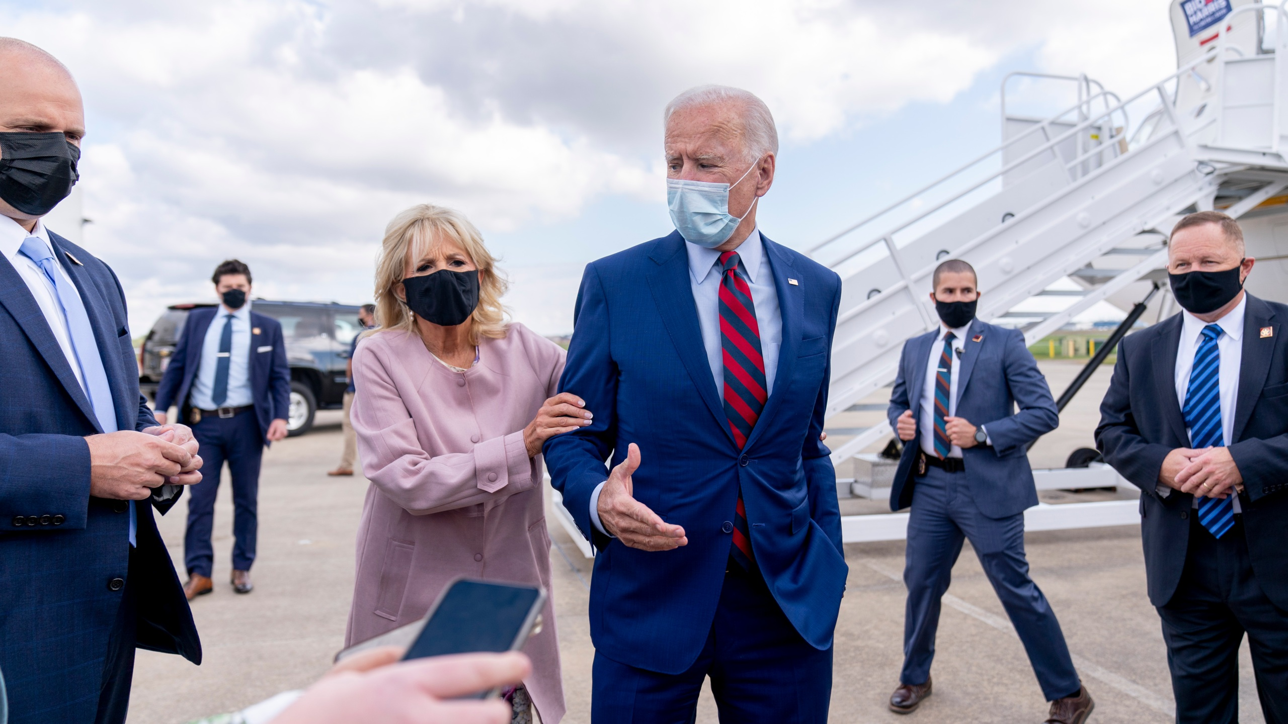 Jill Biden moves her husband, Democratic presidential candidate former Vice President Joe Biden, back from members of the media as he speaks outside his campaign plane at New Castle Airport in New Castle, Del., Monday, Oct. 5, 2020, to travel to Miami for campaign events. (AP Photo/Andrew Harnik)