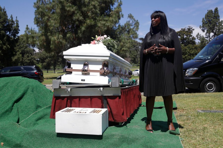 In this July 21, 2020, file photo, Candy Boyd, owner of Boyd Funeral Home, speaks to family members at an interment for Lydia Nunez, who died from COVID-19, at the Rose Hills Cemetery in Whittier, Calif. (AP Photo/Marcio Jose Sanchez, File)