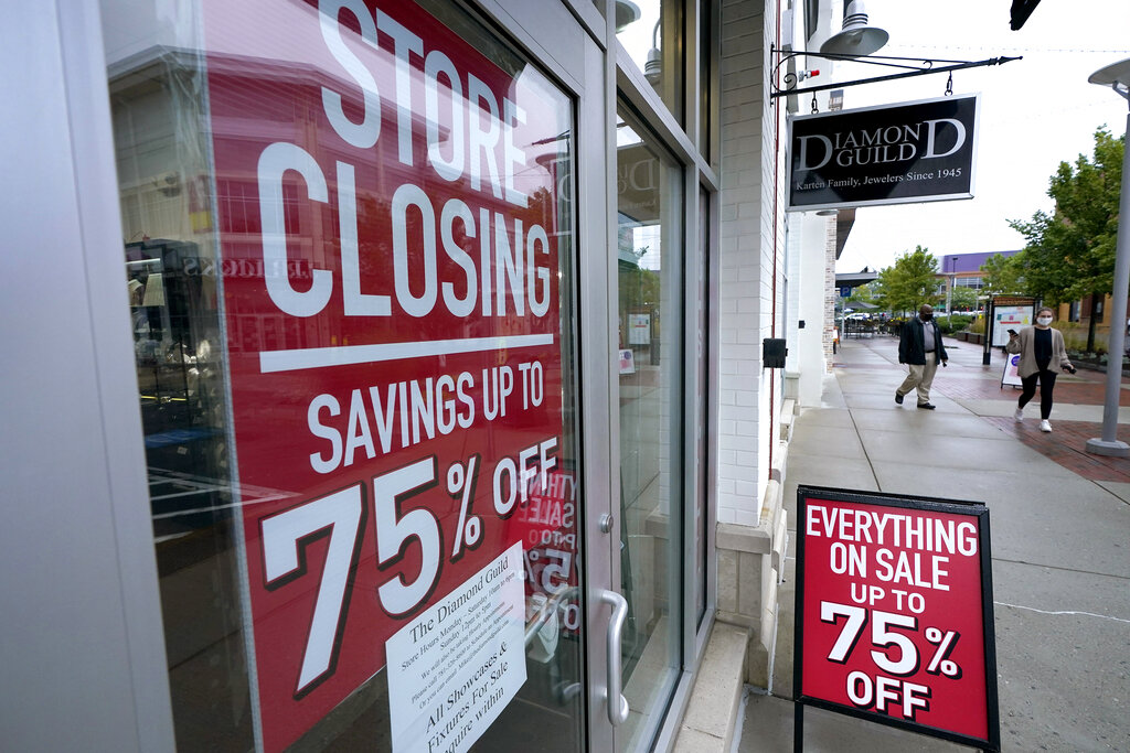 In this Wednesday, Sept. 2, 2020, file photo, passers-by walk past a business storefront with store closing and sale signs in Dedham, Mass. U.S. employers advertised for slightly fewer jobs in August while their hiring ticked up modestly. (AP Photo/Steven Senne, File)