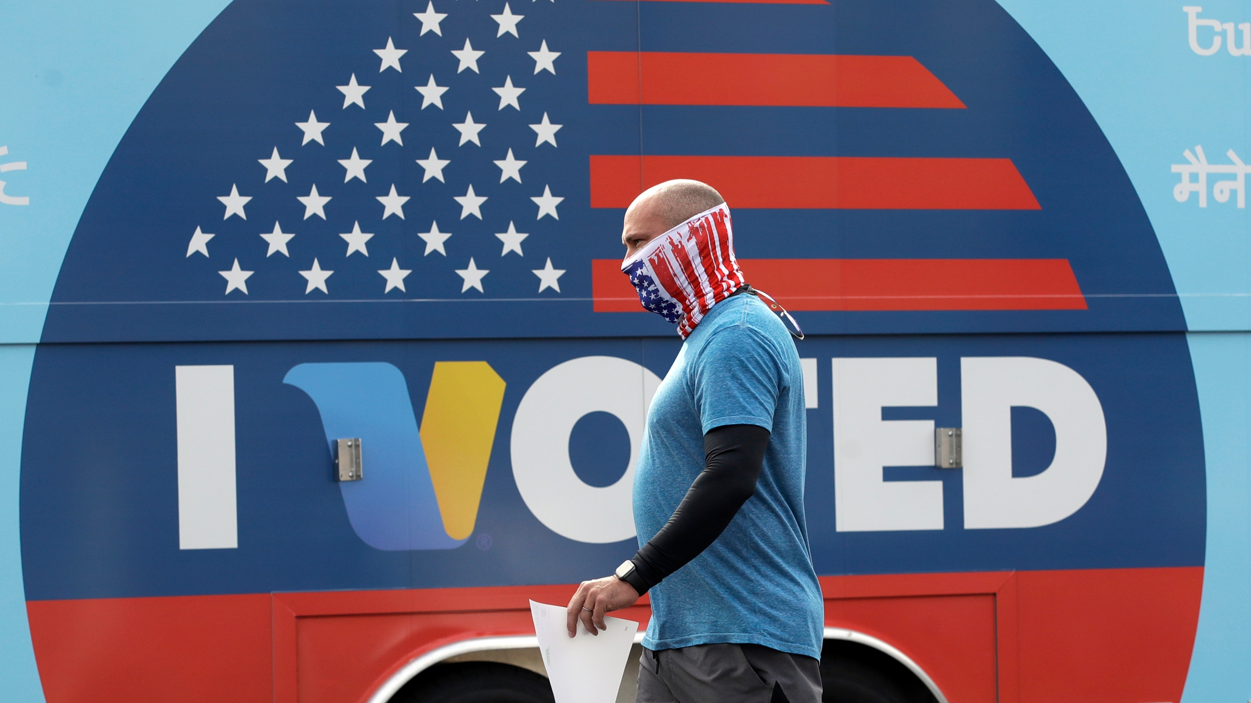 In this May 12, 2020 file photo, Robb Rehfeld wears a mask as he walks to cast his vote during a special election for California's 25th Congressional District seat in Santa Clarita, Calif. With a divided nation on edge as Election Day approaches, California is warning local election officials to prepare for disruption at polling places and potential cases of voters being intimidated or blocked from casting ballots. (AP Photo/Marcio Jose Sanchez, File)