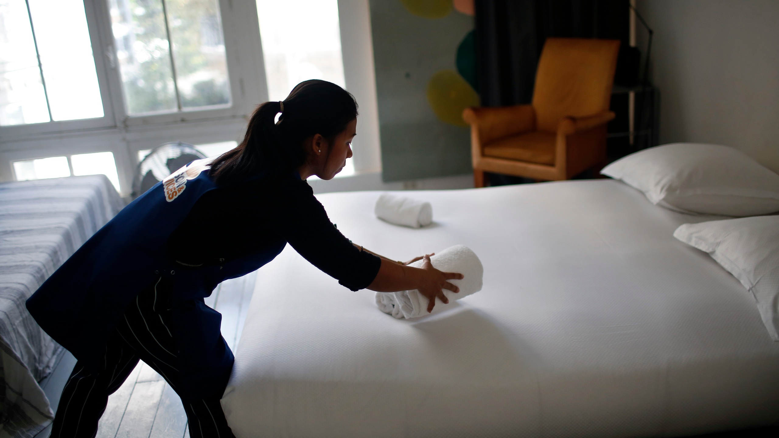 In this Thursday, Sept. 20, 2018 photo, a cleaning lady works in an apartment located on Airbnb in Paris. Airbnb said Thursday, Oct. 8, 2020 it will require hosts to comply with enhanced cleaning procedures as part of its effort to reassure guests and local officials during the coronavirus pandemic. (AP Photo/Thibault Camus, file)