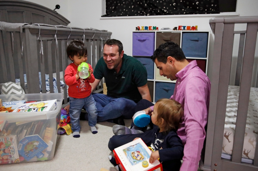 In this Jan. 23, 2020, file photo, Elad Dvash-Banks, right, and his partner Andrew, play with their twin sons, Ethan, left, and Aiden in their apartment in Los Angeles. (AP Photo/Jae C. Hong, File)