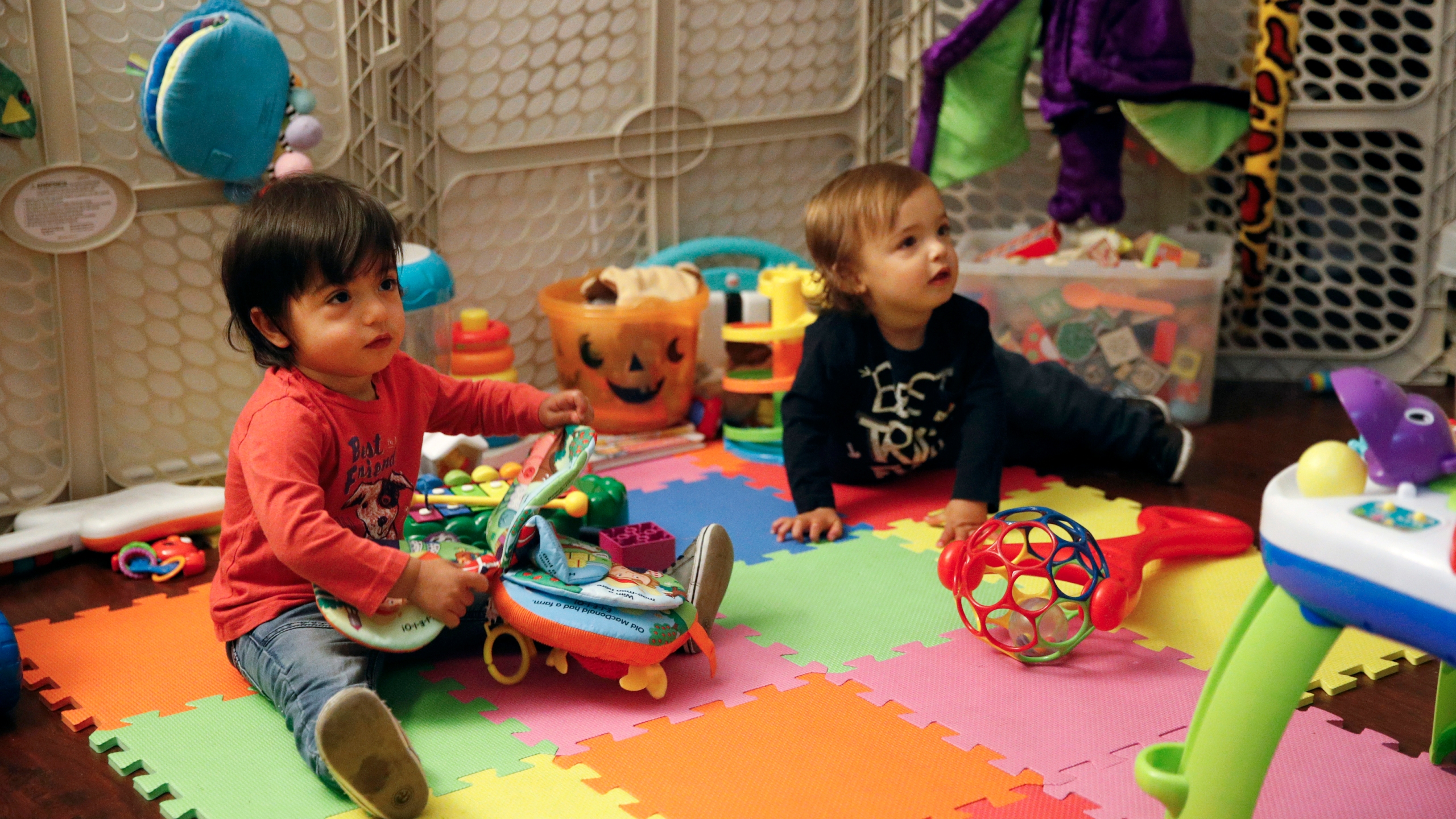 In this Jan. 23, 2018, file photo, 16-month-old Ethan Dvash-Banks, left, and his twin brother Aiden play in the living room of their apartment in Los Angeles. (AP Photo/Jae C. Hong, File)