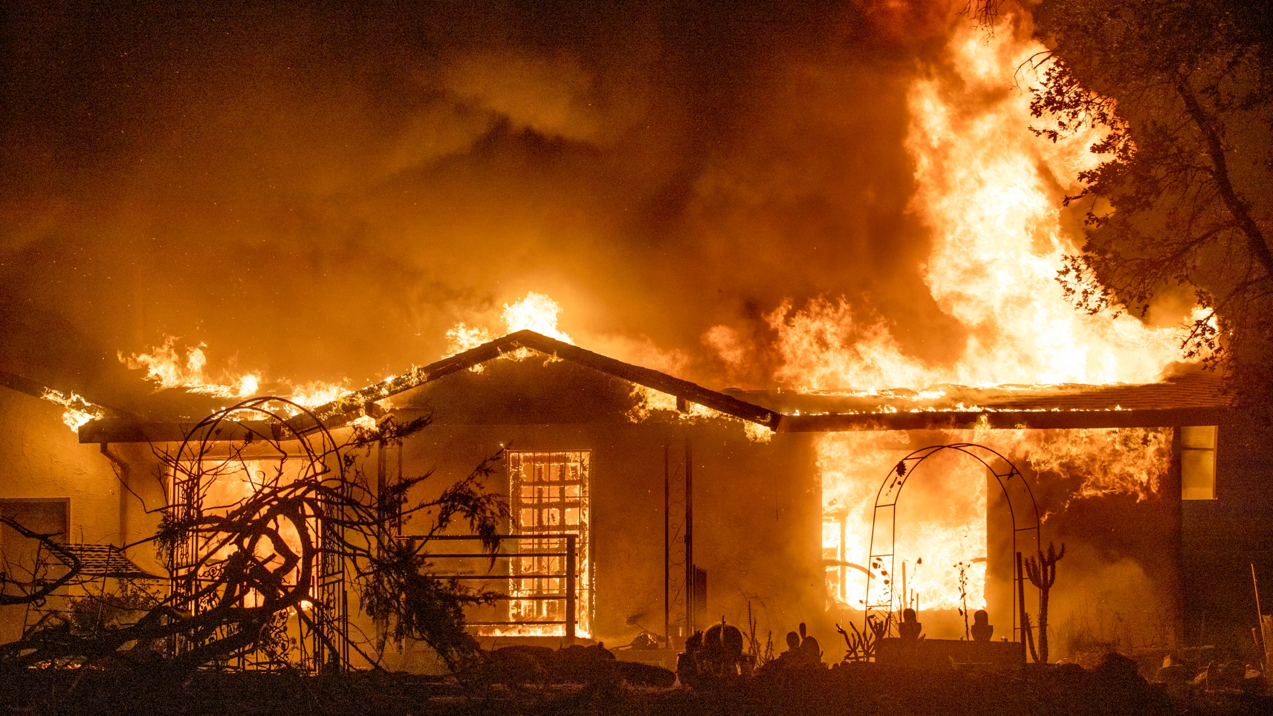 In this Sept. 27, 2020, file photo, a house burns on Platina Road at the Zogg Fire near Ono, Calif. (AP Photo/Ethan Swope, File)
