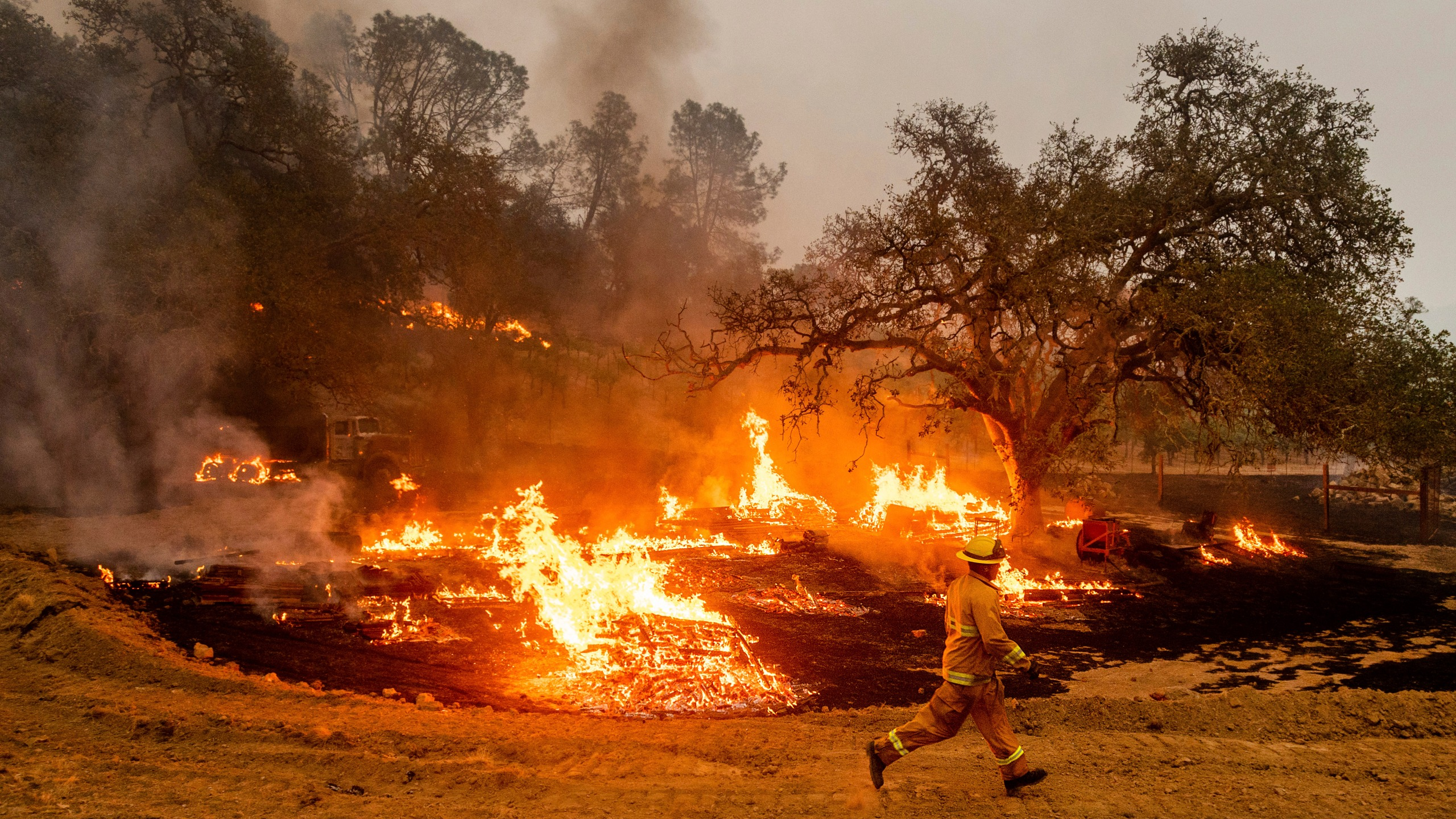A firefighter runs past flames while battling the Glass Fire in a Calistoga vineyard on Oct. 1, 2020. (Noah Berger / Associated Press)