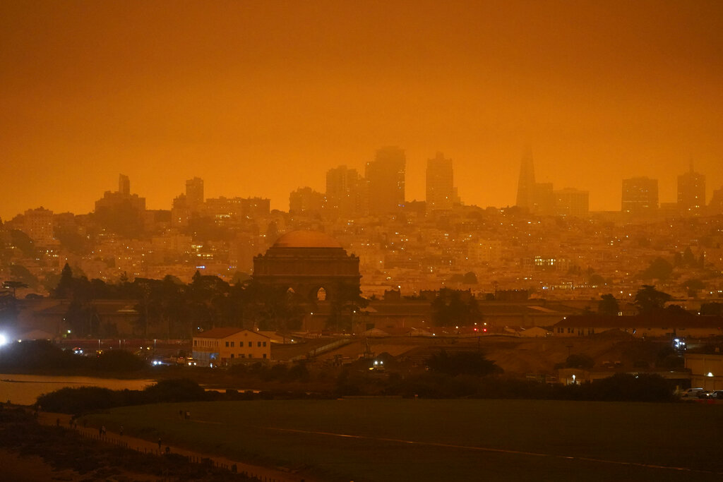 In this Sept. 9, 2020, file photo, taken at 11:18 a.m., is a dark orange sky above Crissy Field and the city caused by heavy smoke from wildfires in San Francisco. (AP Photo/Eric Risberg, File)