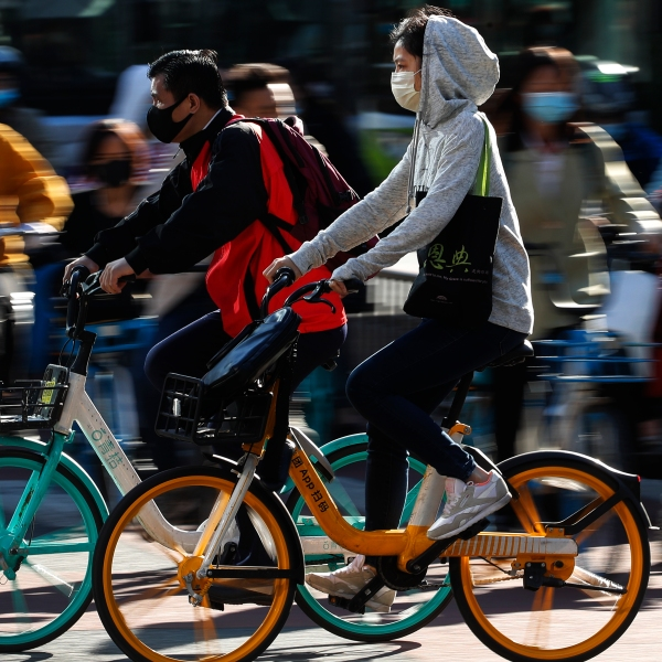 People wearing face masks to help curb the spread of the coronavirus ride bicycle during the morning rush hour in Beijing, Monday, Oct. 12, 2020. (AP Photo/Andy Wong)