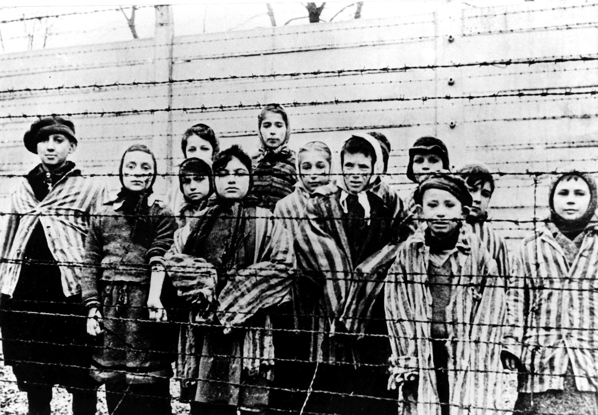 A picture taken just after the liberation by the Soviet army in January, 1945, shows a group of children wearing concentration camp uniforms at the time behind barbed wire fencing in the Oswiecim (Auschwitz) nazi concentration camp. (AP Photo/CAF pap, file)