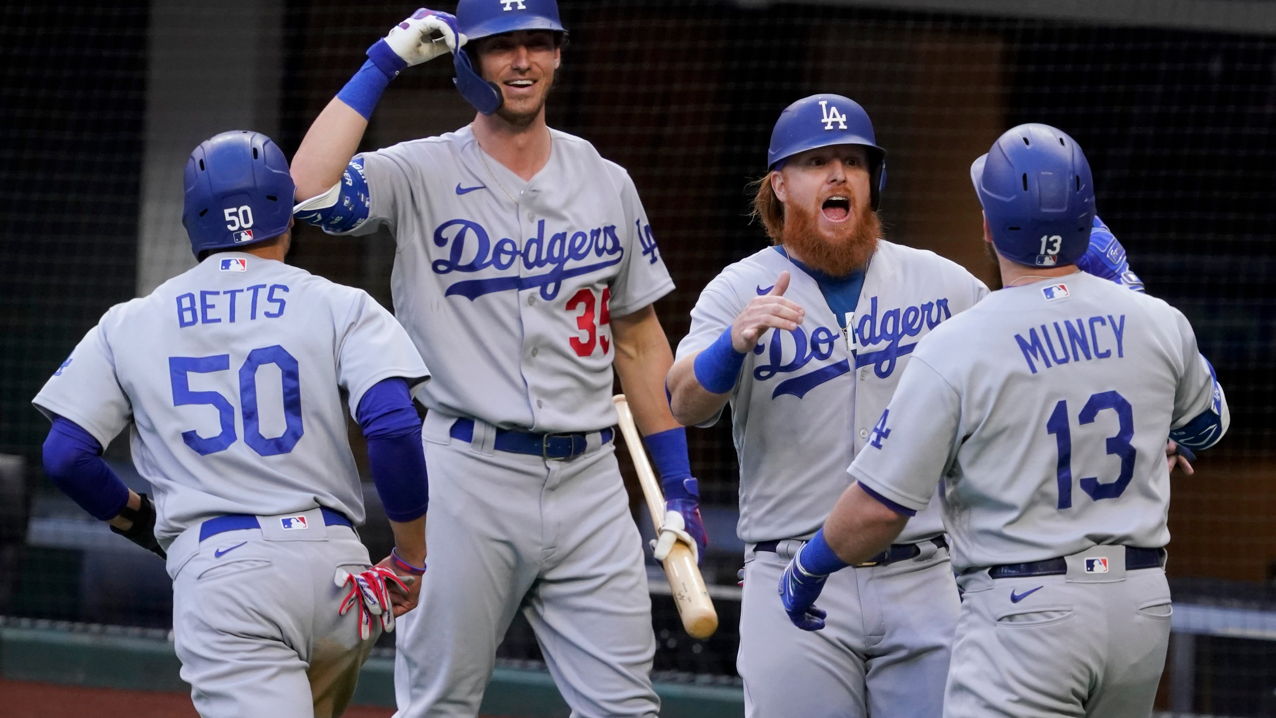 Los Angeles Dodgers' Max Muncy (13) celebrates his grand slam home run during the first inning in Game 3 of a baseball National League Championship Series against the Atlanta Braves on Oct. 14, 2020, in Arlington, Texas. (AP Photo/Tony Gutierrez)