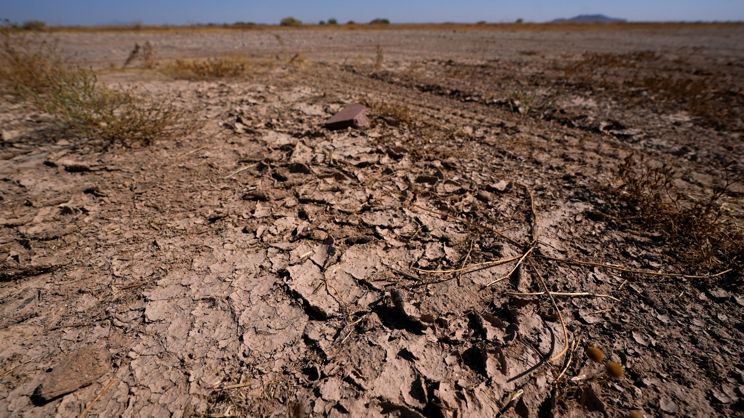 In this Wednesday, Sept. 30, 2020 file photo, dry desert soil cracks due to the lack of monsoon rainfall in Maricopa, Ariz. In a report released on Thursday, Oct. 15, 2020, National Oceanic and Atmospheric Administration forecasters see a dry winter for all of the south from coast-to-coast and say that could worsen an already bad drought. (AP Photo/Ross D. Franklin)