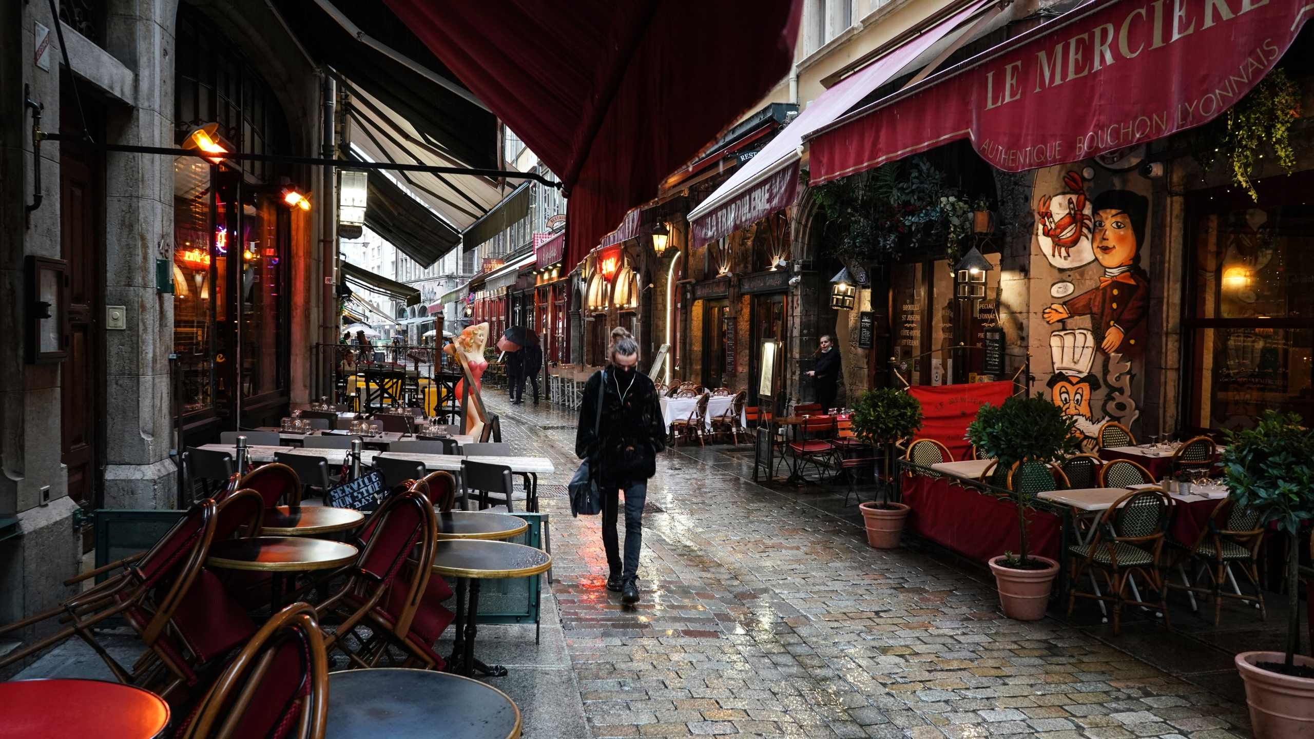 In this Friday, Oct. 2, 2020 file photo, a woman walks by empty restaurants in the center of Lyon, central France. (AP Photo/Laurent Cipriani, File)
