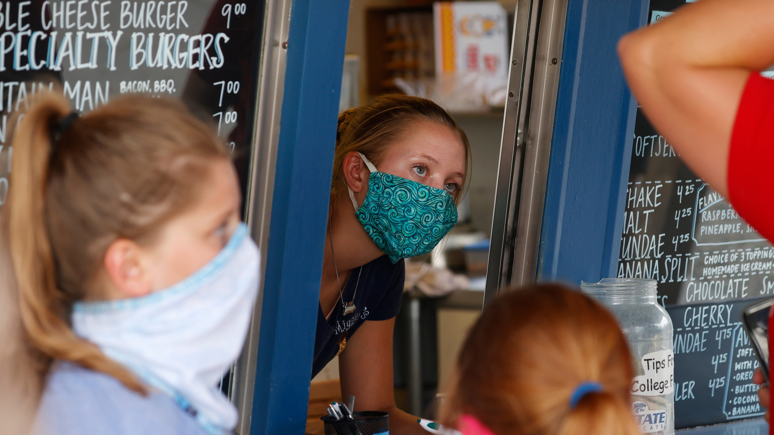 In this Aug. 4, 2020 file photo, a staffer wears a mask while taking orders at a small restaurant in Grand Lake, Colo., amid the coronavirus pandemic. (AP Photo/David Zalubowski, File)