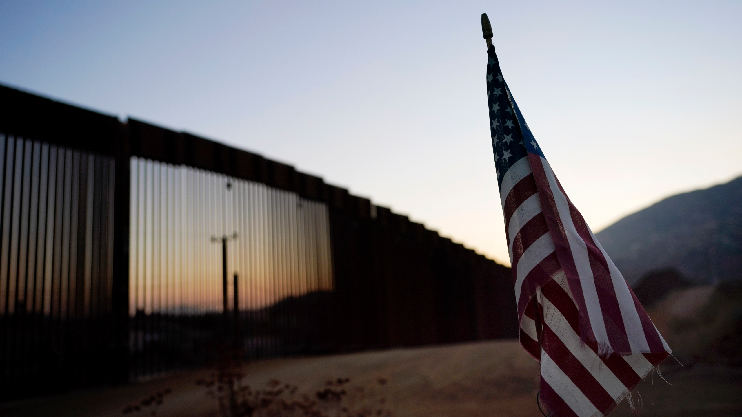 """A flag sits just north of a new section of the border structure, behind, Thursday, Sept. 24, 2020, near Tecate, Calif. President Donald Trump's reshaping of U.S. immigration policy may be most felt in his undoing of asylum. With immigration laws temporarily suspended at the border during the pandemic, people who enter the U.S. illegally are immediately """"expelled"""" without even a piece of paper to record the incident. (AP Photo/Gregory Bull)"""