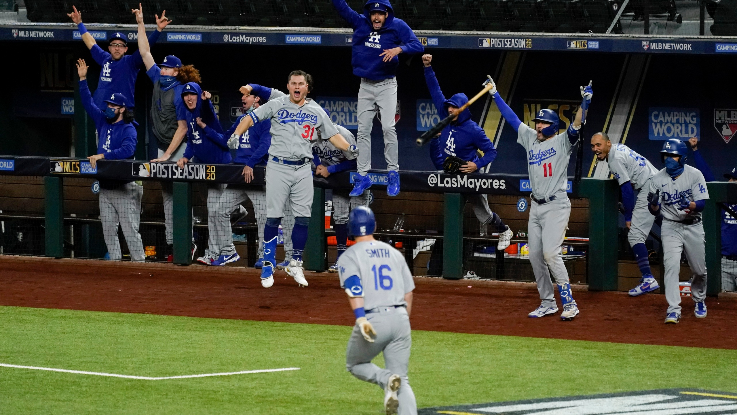 The Los Angeles Dodgers celebrate a three-run home run by Will Smith against the Atlanta Braves during the sixth inning in Game 5 of a baseball National League Championship Series on Oct. 16, 2020, in Arlington, Texas. (AP Photo/Tony Gutierrez)