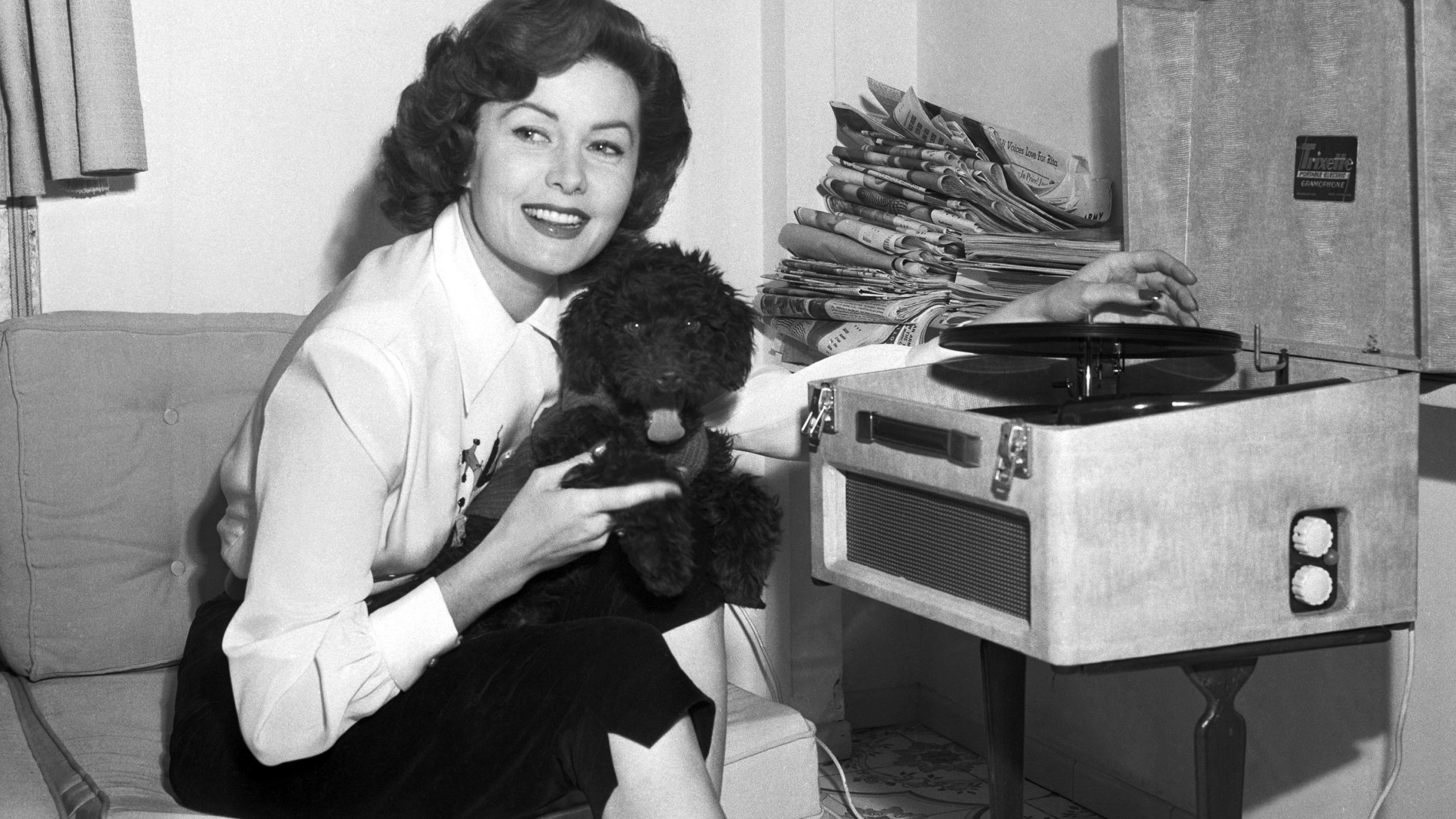 In this March 1, 1955, file photo, Actress Rhonda Fleming reads in her penthouse apartment in Rome. (AP Photo/Jim Pringle, File)
