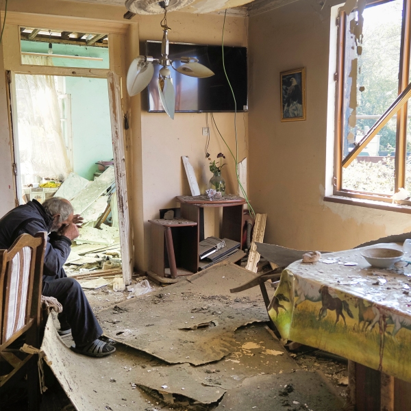 Yury Melkonyan, 64, sits in his house damaged by shelling from Azerbaijan's artillery during a military conflict in Shosh village outside Stepanakert, the capital of Nagorno-Karabakh on Oct. 17, 2020. (AP Photo)