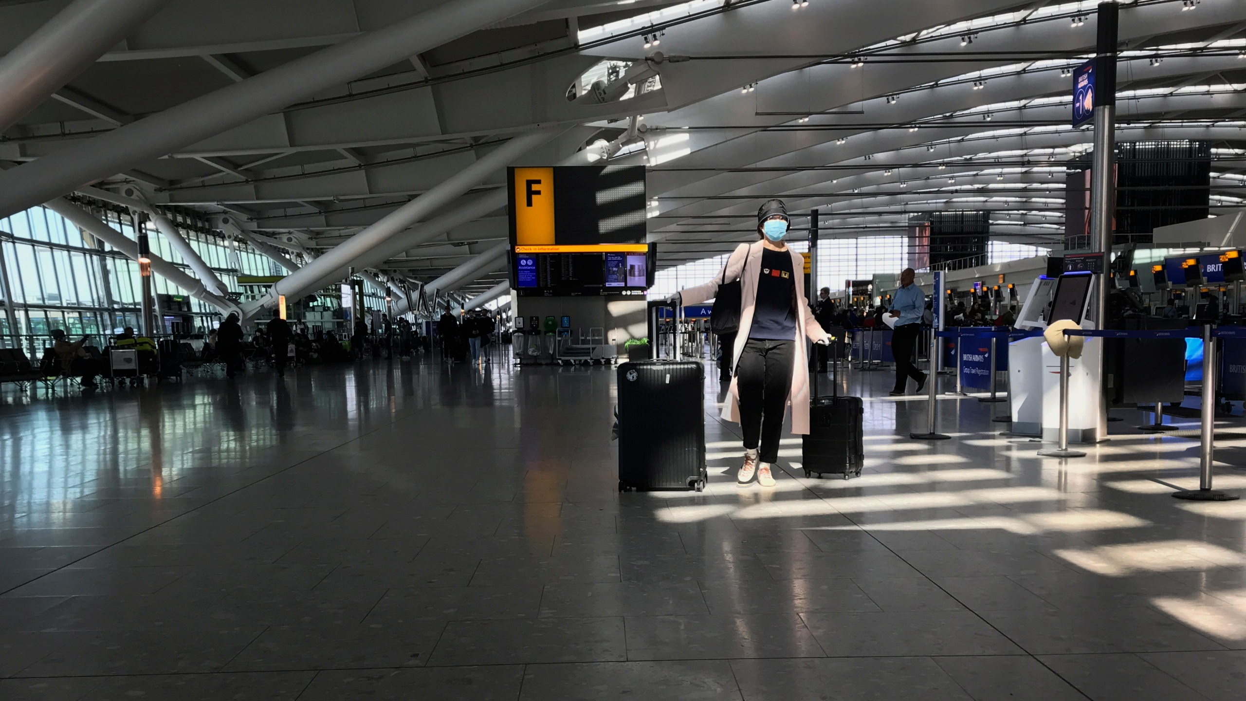 In this Tuesday, March 24, 2020 file photo, a woman wears a mask as she walks through a quieter than usual Heathrow Airport Terminal 5, in London. Air traffic is down 92% this year as travelers worry about catching COVID-19 and government travel bans and quarantine rules make planning difficult. One thing airlines believe could help is to have rapid virus tests of all passengers before departure. (AP Photo/Kirsty Wigglesworth, File)
