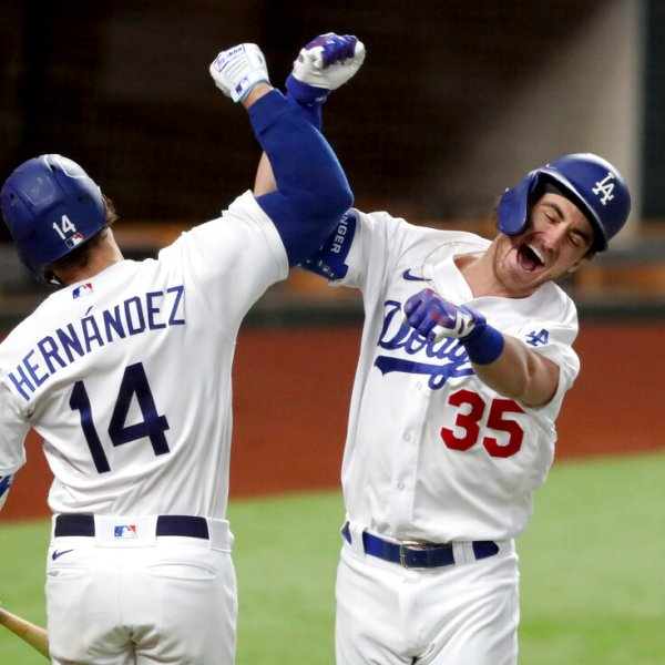 Los Angeles Dodgers' Cody Bellinger, right, celebrates his solo home run with Enrique Hernandez against Atlanta Braves relief pitcher Chris Martin during the seventh inning in Game 7 of a baseball National League Championship Series on Oct. 18, 2020, in Arlington, Texas. (Curtis Compton/Atlanta Journal-Constitution via AP)