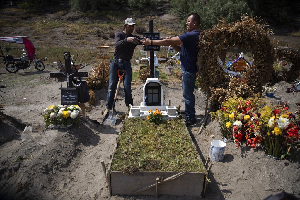 Cemetery worker Jorge Arvizu, left, helps a family member place a plaque on the grave of Vicente Dominguez who died of complications related to the new coronavirus, at the municipal cemetery Valle de Chalco, on the outskirts of Mexico City, on Oct. 20, 2020. (AP Photo/Marco Ugarte)