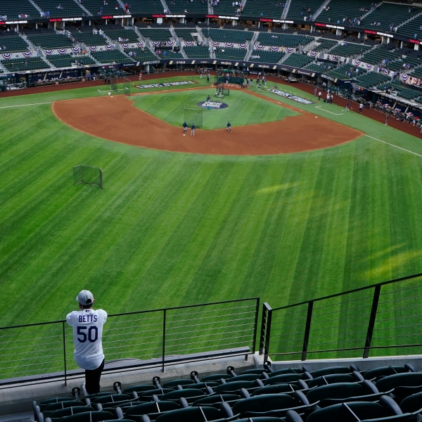 A fan watches batting practice from center field before Game 1 of the baseball World Series between the Los Angeles Dodgers and the Tampa Bay Rays on Oct. 20, 2020, in Arlington, Texas.(AP Photo/Sue Ogrocki)