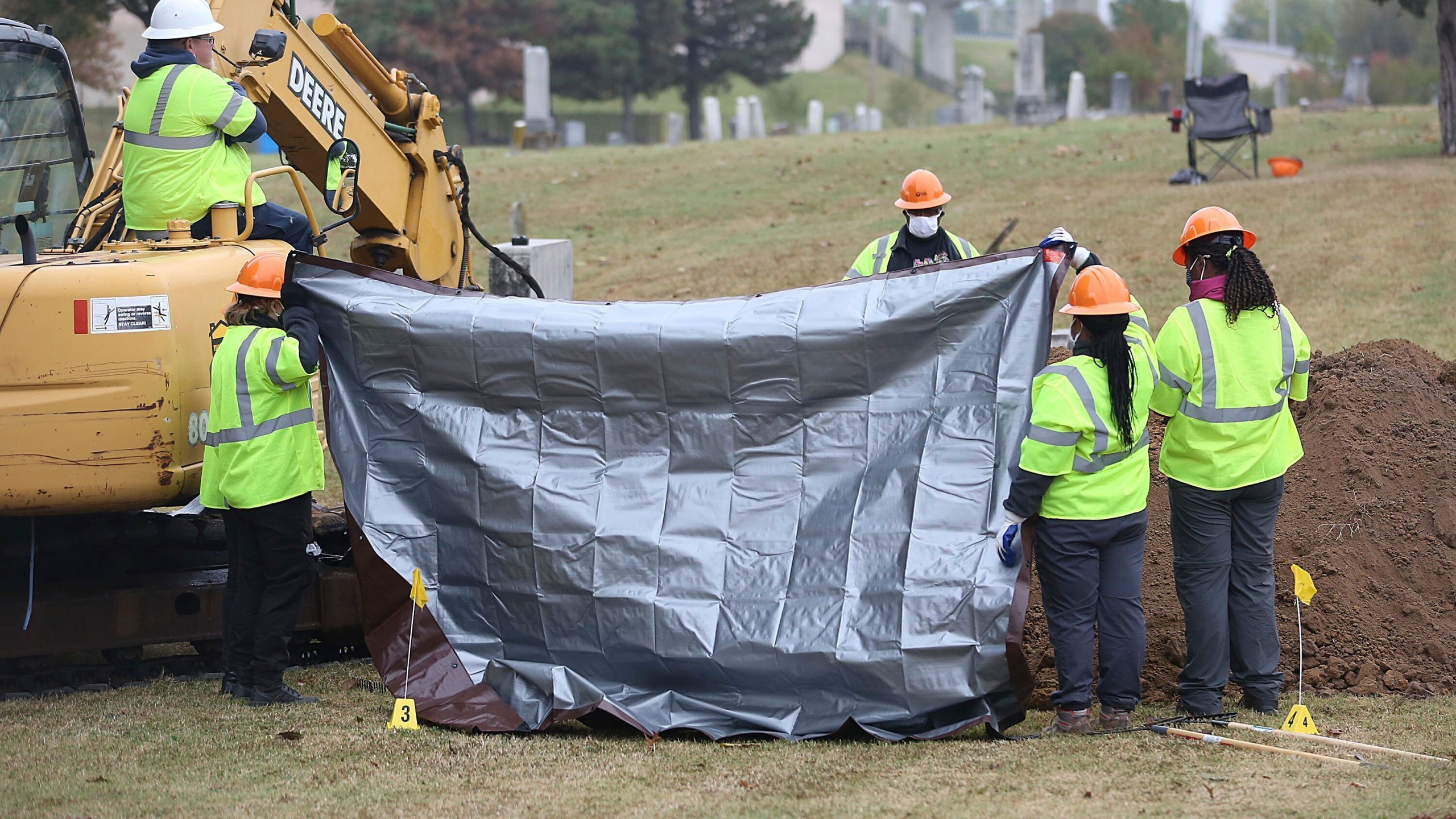 Workers hold up tarps to block spectators' views during a second test excavation and core sampling, Tuesday, Oct. 20, 2020, in the search for remains at Oaklawn Cemetery in Tulsa, Okla., from the 1921 Tulsa Race Massacre. (Mike Simons/Tulsa World via AP)