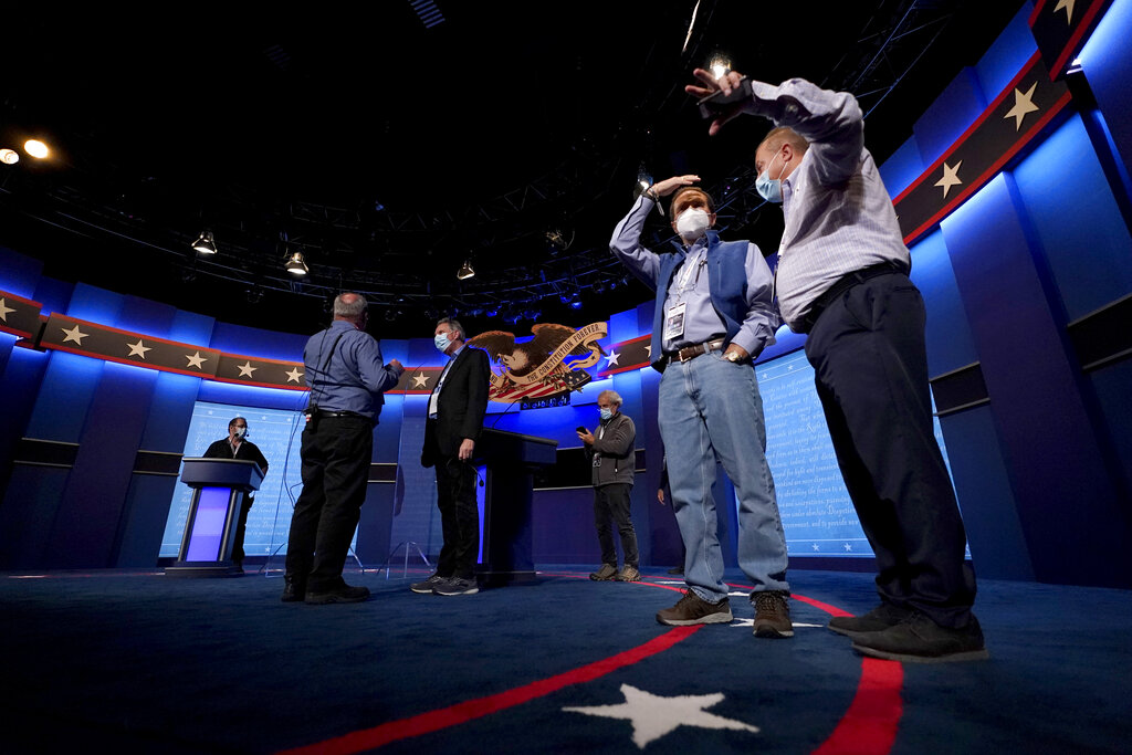 Production crew member stand on stage ahead of the final presidential debate between Republican candidate President Donald Trump and Democratic candidate former Vice President Joe Biden, Wednesday, Oct. 21, 2020, in Nashville, Tenn. (AP Photo/Julio Cortez)