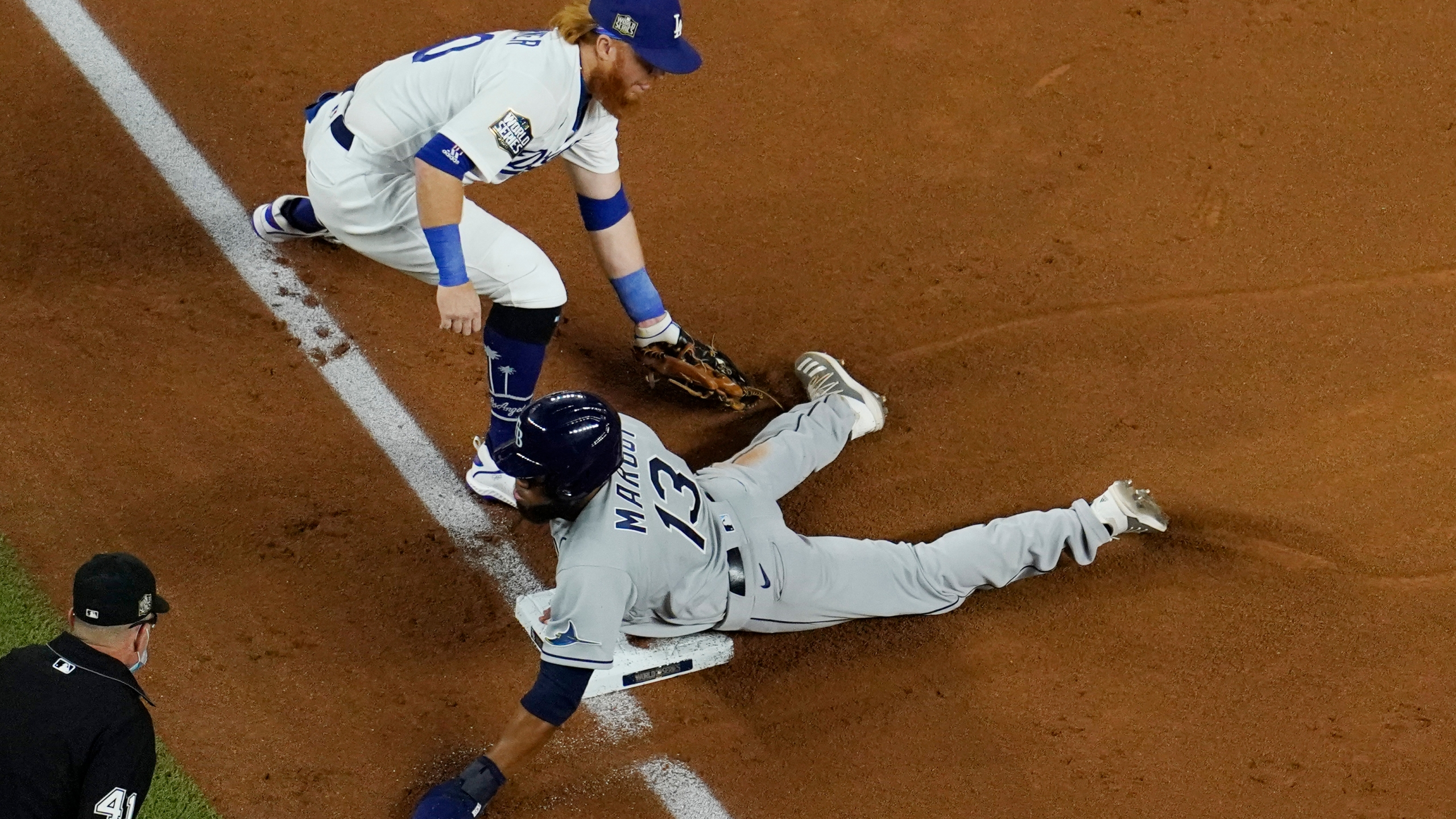 Tampa Bay Rays' Manuel Margot is safe at third past Los Angeles Dodgers third baseman Justin Turner on a ball hit by Joey Wendle during Game 2 of the World Series on Oct. 21, 2020, in Arlington, Texas. (David J. Phillip / Associated Press)