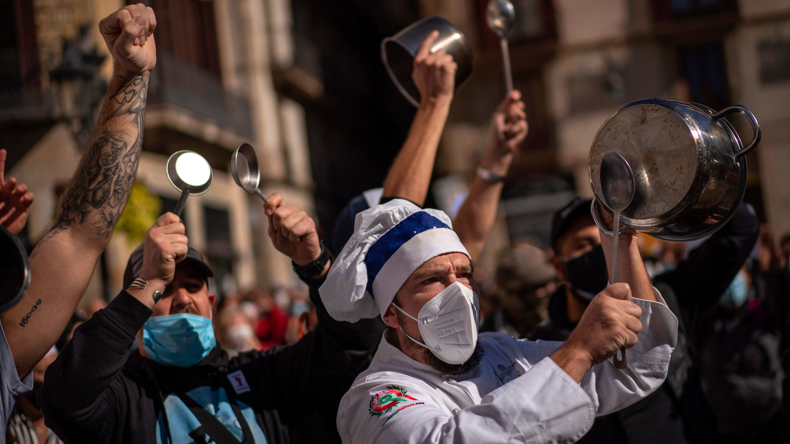 In this Friday, Oct. 16, 2020 file photo, workers of catering sectors take part in a protest organized by restaurants and bar owners in Barcelona, Spain. (AP Photo/Emilio Morenatti, File)