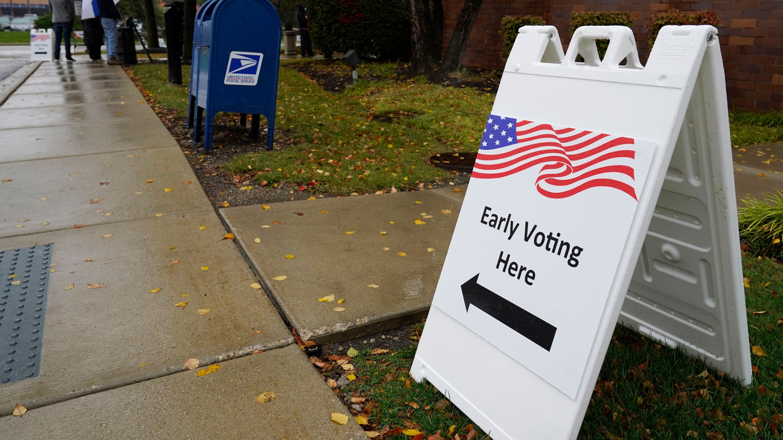 An information sign shows outside the Elk Grove Village Hall as voters wait in line during early voting at Elk Grove Village, Ill., Friday, Oct. 23, 2020. (AP Photo/Nam Y. Huh)