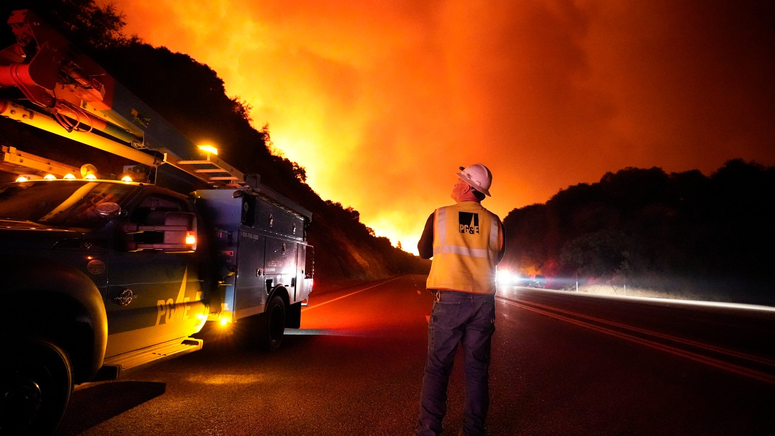 In this Sept. 8, 2020, file photo, a Pacific Gas and Electric worker looks up at the advancing Creek Fire along Highway 168 near Alder Springs, Calif.(AP Photo/Marcio Jose Sanchez, File)