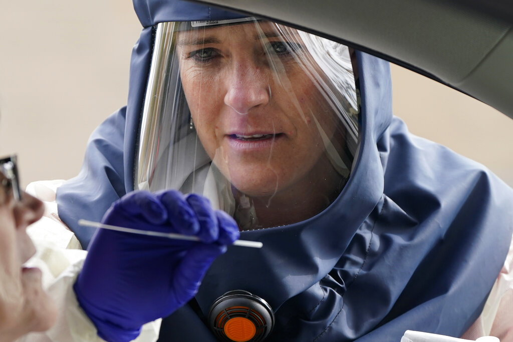 In this Friday, Oct. 23, 2020, file photo, Salt Lake County Health Department public health nurse Lee Cherie Booth performs a coronavirus test outside the Salt Lake County Health Department in Salt Lake City. (AP Photo/Rick Bowmer, File)